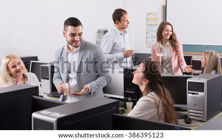 Group of smiling colleagues drinking champagne at office