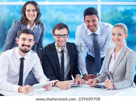 Group of smiling colleagues with touchpads looking at camera in office