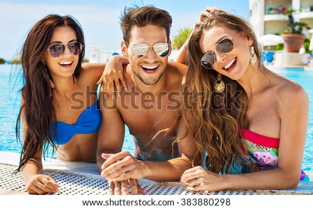 Group Of Smiling Friends Having Fun In Swimming Pool And Wearing Sunglasses