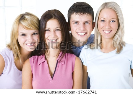 Group of smiling friends looking at camera. Closeup on faces. Front view.