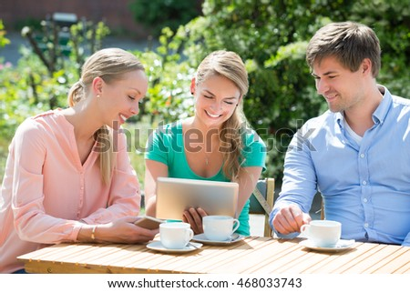 Group Of Smiling Friends Looking At Digital Tablet With Cup Of Coffee On Table