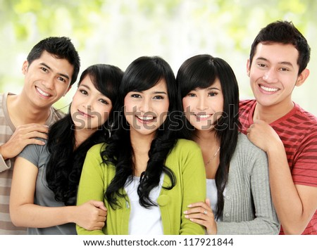 group of smiling friends staying together and looking at camera