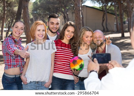 Group of smiling friends taking pictures together at countryside