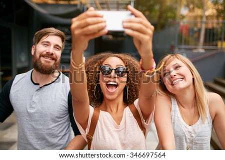 Group of smiling friends taking selfie with mobile phone. Multiracial man and women enjoying themselves outdoors and taking pictures with smart phone. - stock photo
