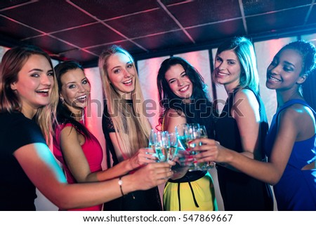 Group of smiling friends toasting glass of champagne at bar