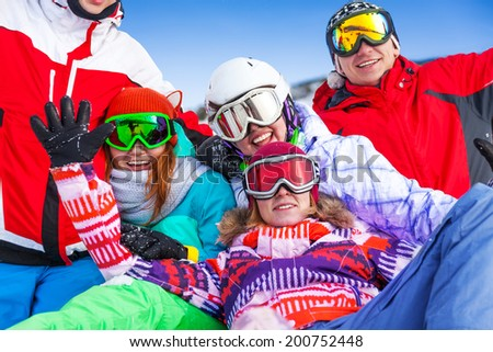 Group of smiling happy snowboarders having fun very close to each other