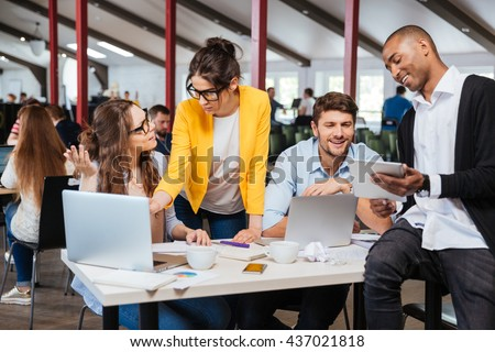 Group of smiling inspired young business people working together in office - stock photo