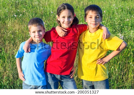Group of smiling kids standing on the green meadow