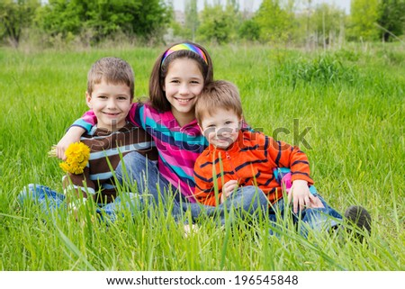 Group of smiling kids with dandelions sitting on the green grass meadow - stock photo
