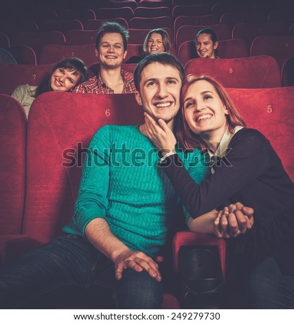 Group of smiling people watching movie in cinema - stock photo