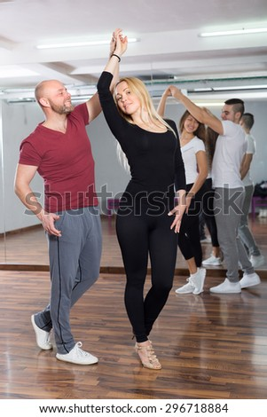 Group of smiling positive young adults dancing salsa at dance class