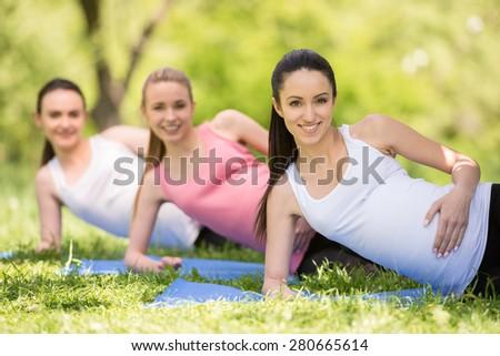 Group of smiling pregnant women doing prenatal yoga. - stock photo
