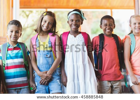 Group of smiling school kids standing in row at school