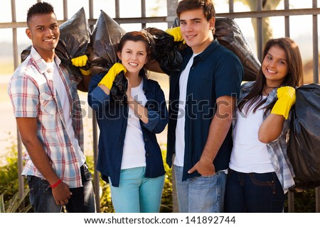 group of smiling teenage volunteers with garbage bags after cleaning the streets - stock photo