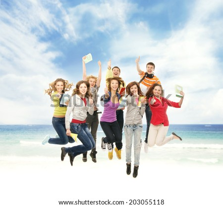 Group of smiling teenagers jumping together over the beach and sea background - stock photo