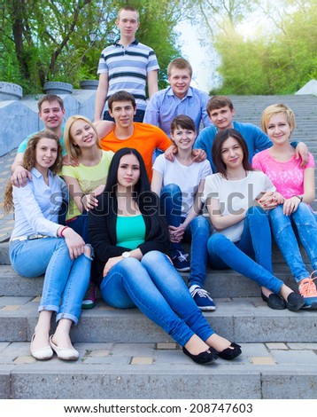 Group of smiling teenagers sitting outdoors. Friendship concept