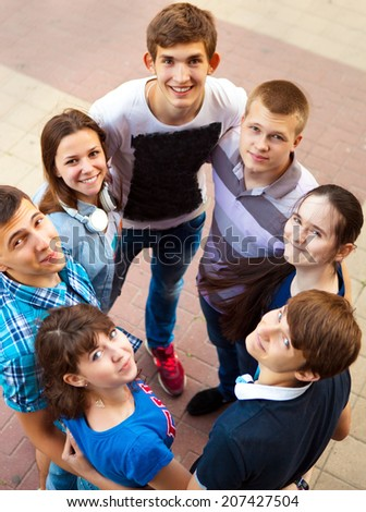 Group of smiling teenagers standing outdoors. Friendship concept