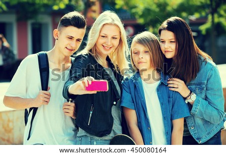 group of smiling teenagers taking mobile self picture with phone in park - stock photo