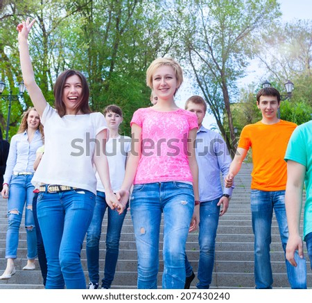 Group of smiling teenagers walking outdoors. Friendship concept