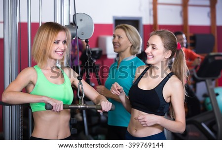 Group of smiling women and man having workout on machines in gym. Selective focus