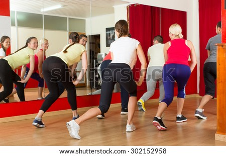 Group of smiling young adults  dancing active dance in a studio