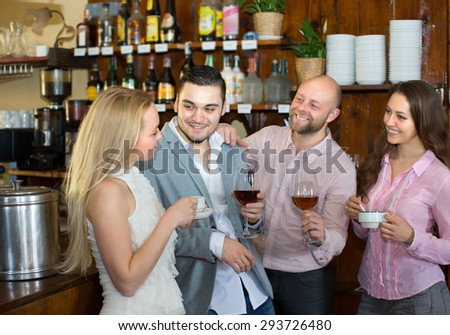 Group of smiling young adults hanging out in bar with drinks. Focus on guy