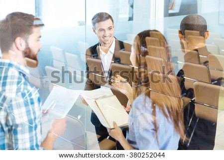 Group of smiling young business people standing and discussing new ideas in conference hall  - stock photo