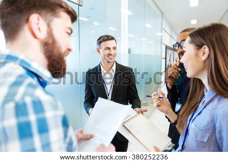 Group of smiling young business people standing and talking with team leader in hall of office