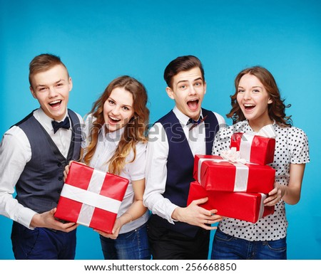 Group of smiling young people holding presents wrapped in red gift paper. Hipster style. Blue background. Standing together happy smile give wrapped giftboxes - stock photo