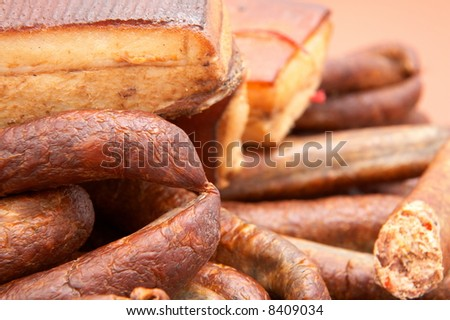 Group of smoked hams and sausages on brown background