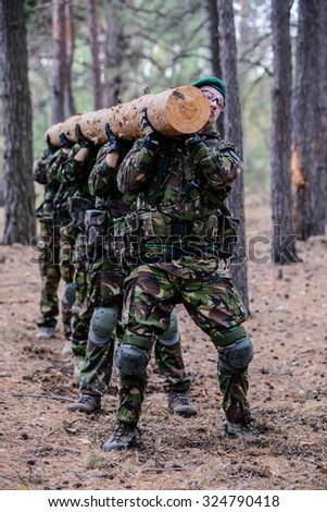 Group of soldiers in the forest holding a big log