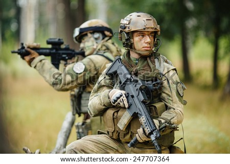 Group of soldiers on patrol at modern battle field in the forest. war, army and people concept