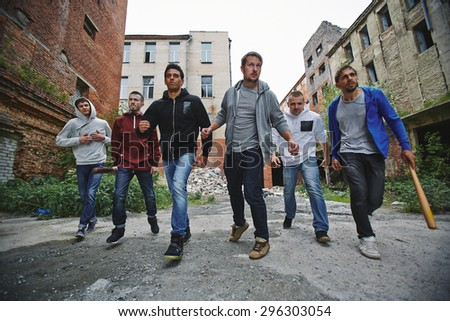 Group of spiteful hooligans walking along grunge brick houses - stock photo