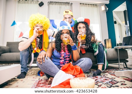Group of sport supporters of several diverse nations watching match on television at home - stock photo