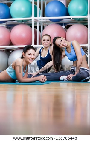 Group of sport women have a rest in the gym centre against set of gymnastic balloons - stock photo