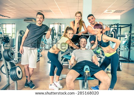 Group of sportive people in a gym - Happy sporty friends in a weight room while training - Concepts about lifestyle and sport in a fitness club - stock photo