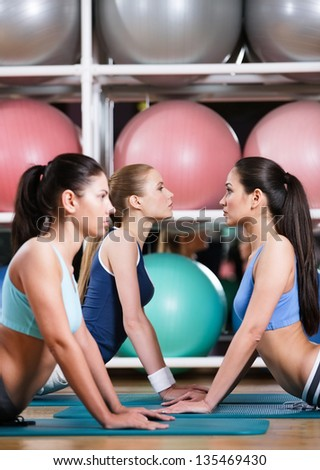 Group of sportive women in the gym centre doing stretching fitness exercise - stock photo