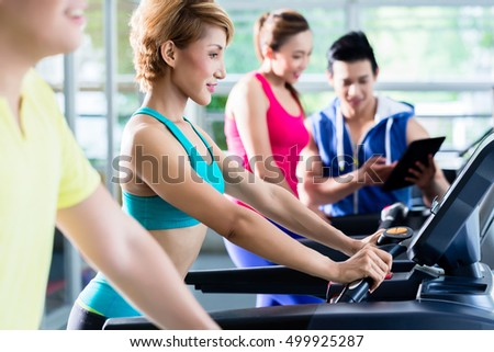 Group of sportive young people during cardio training on treadmill under supervision of trainer with tablet