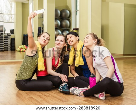 Group of sportive young women making selfie using smartphone in the fitness club after training - stock photo