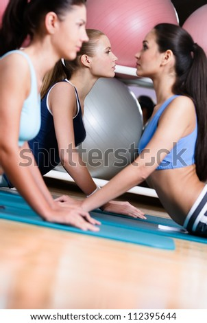 Group of sportswomen in the gym class doing stretching fitness exercise - stock photo
