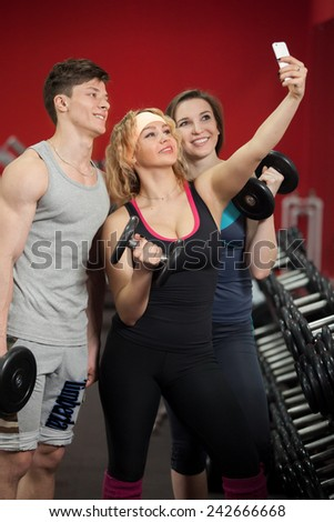 Group of sporty caucasian people, young man and two girls, taking selfie with dumbbells in gym - stock photo