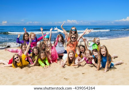 Group of sporty children playing on the beach - stock photo