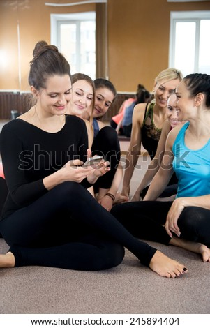 Group of sporty young female friends laughing, using mobile phone, touching the screen of smart phone, texting while resting after practice, on break between exercises in sports club - stock photo