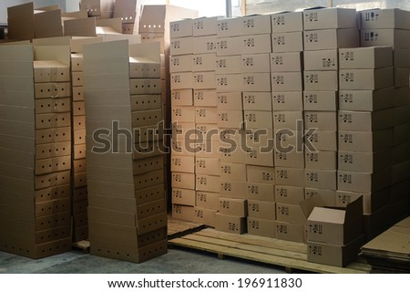group of stacked cardboard boxes on wooden pallets  in factory warehouse - stock photo