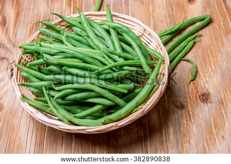 group of string beans also call green bean in a bamboo basket on a wooden table - stock photo