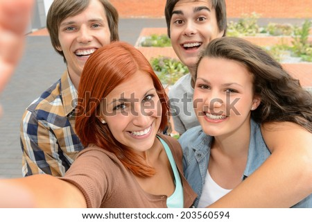 Group of student teenage friends taking selfie laughing at camera - stock photo