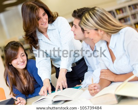 Group of students at the library asking advise to a librarian - stock photo