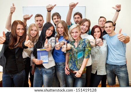 Group of students at the university with thumbs up - stock photo