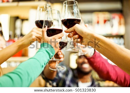 Group of students cheering with red wine at aperitif dinner bar - Young cheerful people toasting drinks in restaurant - Good and positive mood with friends concept - Focus on hand with green pullover