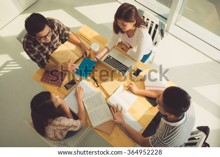 Group of students discussing homework, view from above - stock photo